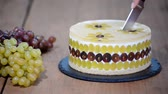 icings : Cutting with a knife mousse cake with grapes. Round mousse cake decorated with grapes.