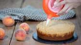 crumble : Cook decorating a cake with icing sugar with a piping bag. Summer peach pie with caramel sugar crumb