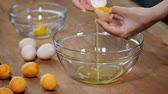 раздельный : Woman hands breaking an egg to separate egg white and yolks and egg shells at the background.