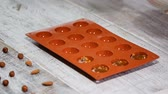 кремний : A woman puts in the silicone mold a caramel and nuts filling.