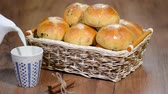 milk pouring : Easter Hot Cross Buns in a Basket. Pour milk into a Cup.