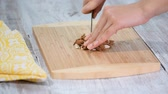 comestível : Female hands cutting almonds on wooden cutting board.