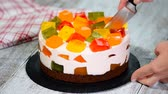 frutoso : Cutting cake with colorful fruity jelly pieces.