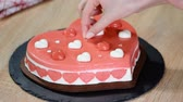 heart shaped : Confectioner decorating heart-shaped mousse cake. Cake for Valentines day.