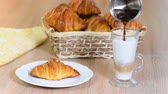 tereyağlı : Women poured espresso in a milk cup to make a latte next to butter croissant Stok Video