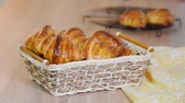 tradicionalmente : Fresh Croissants in a wicker basket on the wooden table Vídeos