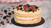 amoras : Confectioner woman decorates berries cake with mint leaves.