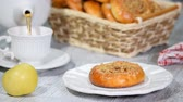 bebida quente : Cup of tea and delicious bun with apple filling. Pouring tea into a cup. Stock Footage