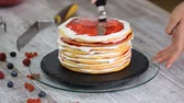 glacé : Woman putting berry paste on cake layer. Making layered cake on cake stand over white backdrop.