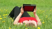 Woman reading a book with a Tablet PC in nature