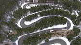 Trucks and cars slowly traversing dangerous bends and turns of a high mountain road pass , in winter time conditions, aerial view