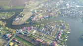 Real estate developments and agricultural surface alongside the shores of a river, aerial view
