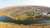 Picturesque village surrounded by lake and natural swamp with specific habitat vegetation , countryside landscape, beginning of spring, aerial view Dostupné videozáznamy