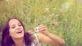 blossoming : Romantic beautiful young smiles woman blowing soap balloons in a flower meadow