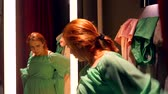 shopaholic : Beautiful young red-haired woman trying on dress in front of mirror in dressing room In clothing store Stock Footage