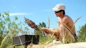 flavour : Young man in sunglasses fry the meat on the beach near the sea. Hot food Shashlik in Russia. Stock Footage