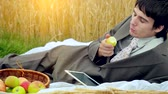 lente : Young handsome businessman use tablet on a picnic in wheat field. 1920x1080 Vídeos