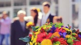 groomsmen : Wedding focused bouquet in the foreground and blurred of newlywed couple having fun in green sunny park. 1920x1080