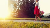 shopaholic : Young woman in beautiful dress with shopping bags goes on the street through the sun during sunset in slowmotion. 1920x1080 Stock Footage