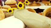 bakery : Composition of rye breads, bag of flour, wicker basket and baguettes with sunflowers on wooden table. 3840x2160