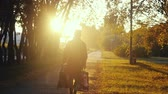 trough : Young woman in a raincoat with shopping bags goes in the park trough the sun during sunset in slowmotion. 1920x1080 Stock Footage