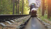 coming in : Young friends walking together on railroad in pines forest in slowmotion. 1920x1080
