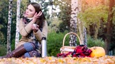 tea : Young beautiful woman sitting on picnic drinking hot tea from a thermal flask in autumn park. Girl sitting on the rug near the pumpkin Halloween theme. 3840x2160 Stock Footage