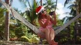 senhora : Young beautiful woman in sunglasses and christmas hat in hammock takes selfie on mobile phone in tropical beach celebrating Christmas. 1920x1080