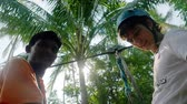 Самуи : Thailand, Koh Samui, 26 january 2016. Funny canyoning instructor explains the tourist man how to hold onto a slingshot and how to slide a rope descent in tropical jungle though the sun. 3840x2160, 4k Стоковые видеозаписи