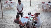 блаженный : Koh Phangan, Thailand, 9 april 2016. Couple sit in beach cafe with menu. Romantic dinner on the beach and waiter stands next to the table. 1920x1080 Стоковые видеозаписи