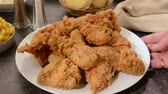 galinha : A platter of fried chicken being set on a table