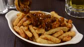fritar : Spooning chili onto french fries Stock Footage