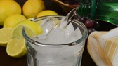 serinletme : Pouring sparkling water into a glass with lemon wedges Stok Video