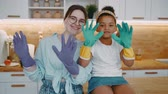 sprzątanie : Mother in glasses and daughter african american girl wearing rubber gloves to clean kitchen wash dishes to protect hands from household chemicals, woman and child in playful mood engage daily routine