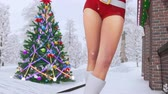 senhora : Close up of attractive blonde girl in sexy Santa Claus suit with outdoor decorated christmas tree and snowy winter forest on a background Vídeos