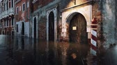 Flooded with water exterior door of ancient venetian building on empty street during catastrophic High Water flood Acqua Alta in Venice, Italy at rainy evening