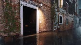 Flooded with water entrance door of ancient venetian building on empty street during anomalous High Water flood Acqua Alta in Venice, Italy at rainy dusk Stock Footage
