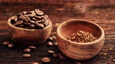 columbian : Delicious coffee. Soluble coffee falling into wooden bowl near bowl with beans on wooden table.