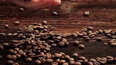 columbian : Fresh roasted coffee beans in female hand on rustic wooden table. Stock Footage