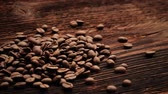 columbian : Coffee beans falling on rustic wooden table. Delicious luxury coffee beans.
