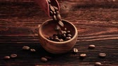 columbian : Coffee beans falling into wooden bowl on rustic brown wooden table. Delicious coffee.