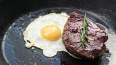 raro : Delicious steak with egg and rosemary cooking on pan.