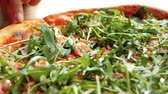 Close up on taking slice of Pizza with arugula on wooden table.