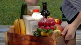 engradado : Delivery man puts fresh groceries in wooden crate on table outdoors in summer. Delivery and groceries. Stock Footage