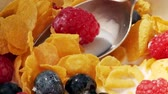 natural yogurt : Eating fresh corn-flakes with silver spoon. Corn-flakes with milk and fruits. Healthy breakfast.