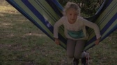 Little girl swinging in hammock outdoors, summertime joy on sunny backyard. Stock Footage