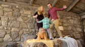 zoon : Happy family with two kids boy and girl siblings todller jumping on the bed and laughing merrily Stockvideo