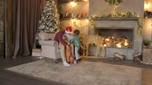 Young father in santa claus dress hanging his children Stok Video