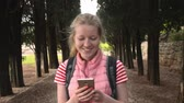 Young caucasian woman with smartphone walking behind trees
