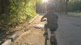 little boy with blue helmet riding bicycle at sunset or sunrise in the park